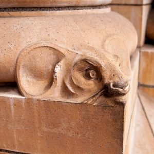 The head of a mouse looks out from the bottom of one of the pillars flanking the entrance.