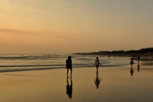 People walk along Kuta beach at sunset