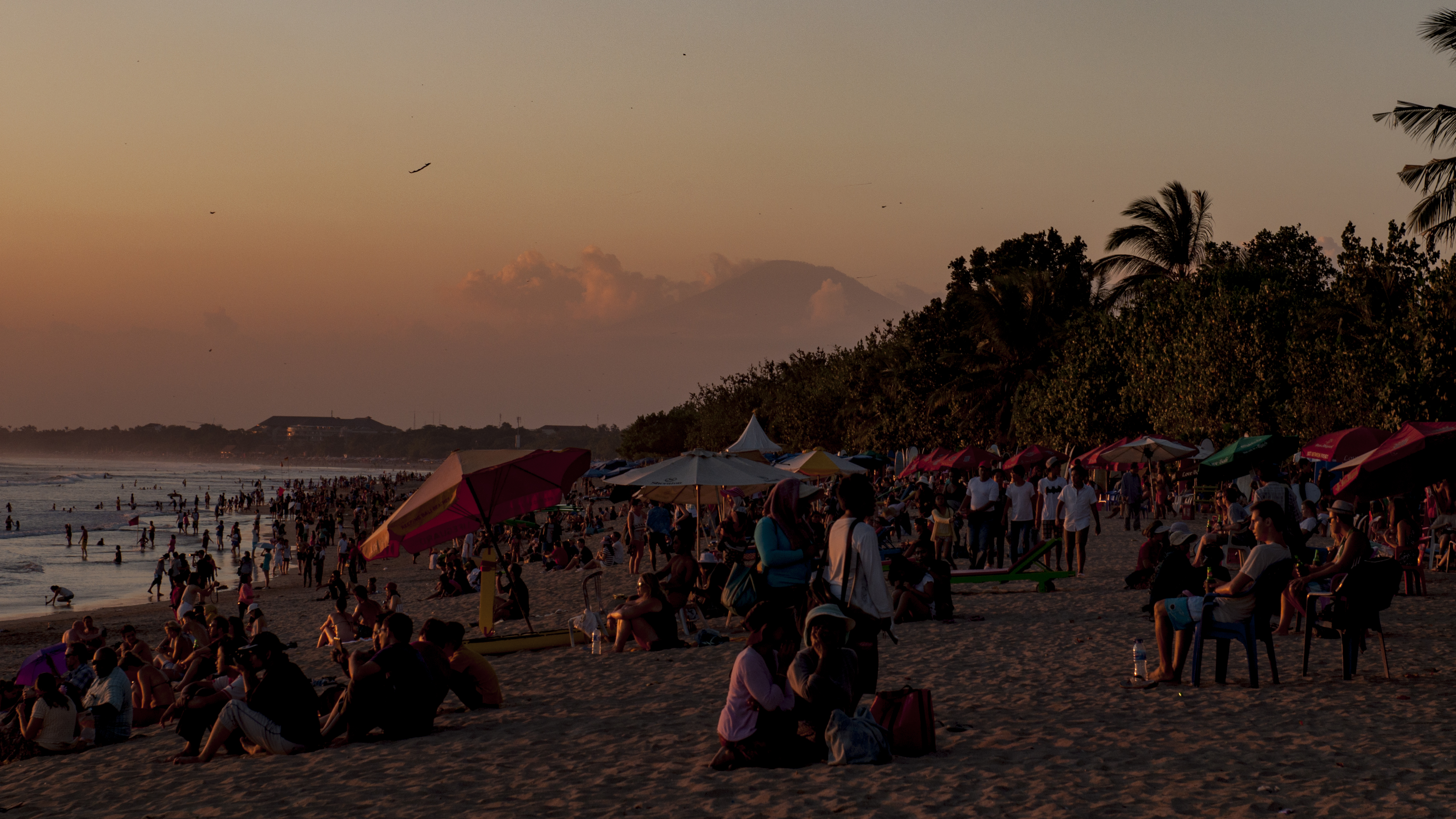 A Volcano Peeps Out From The Clouds As The Crowds Gather To Watch Sunset  From Kuta