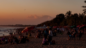 A volcano peeps out from the clouds as the crowds gather to watch sunset from Kuta Beach.