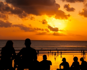 People are silhouetted against the sunset over Kuta Beach