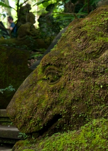 A lion statue lies in wait covered in moss in Ubud's Monkey Forest in Bali